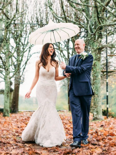 Bride and Groom joyfully walking towards camera under a parasol umbrella through an alley of trees with Autumn leaves on the ground Rhinefield house New Forest