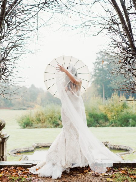 Fine Art editorial portrait of Bride sporting a vintage Edwardian umbrella at a Winter wedding at Rhinefield house New Forest
