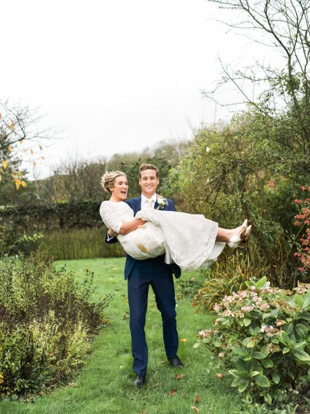Groom walking to camera carrying Bride over a wet lawn at a Winter wedding at a Dorset Farm