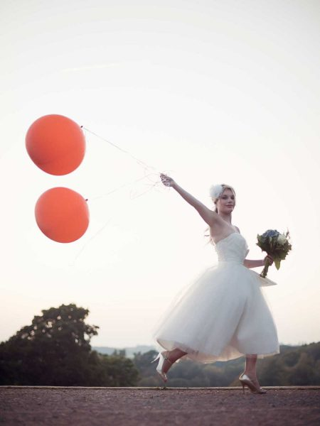 Editorial fashion vintage Bride leaping through holding giant orange balloons wearing 50s short dress and gold shoes