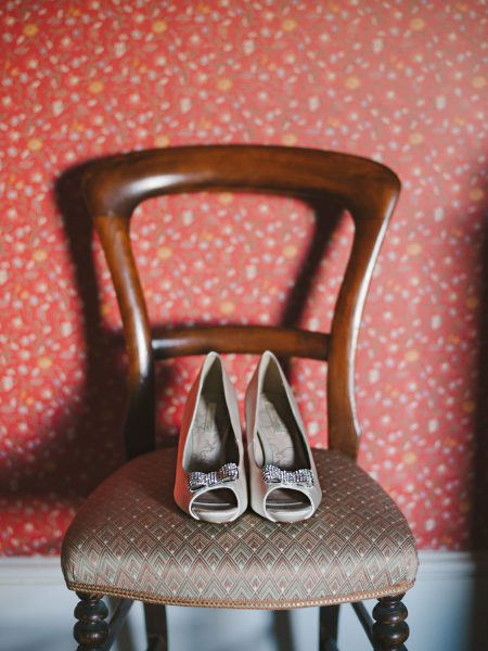 Bow wedding shoes sitting on an antique chair against a red floral wallpaper for a London wedding