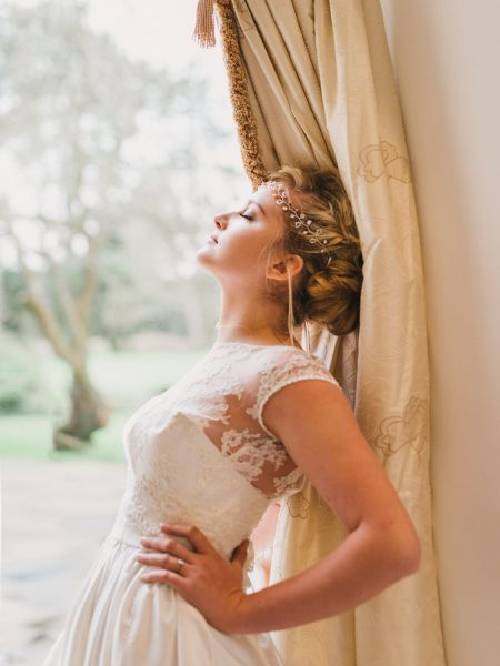Editorial Fine Art portrait of Bride leaning against curtain with hands on hips and eyes closed enjoying sun coming though window for campaign for Katie Elizabeth Bridal Head piece shoot