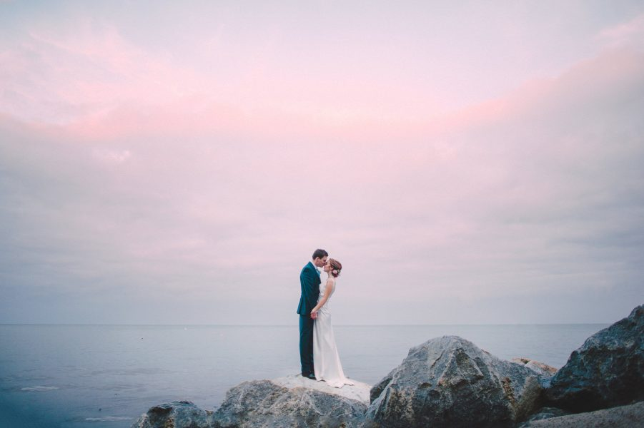Fine Art portrait of Bride and Groom standing on a dramatic black rock kiss with the sea and pink clouds behind them at their relaxed creative cliff wedding Robins Hood Bay Yorkshire