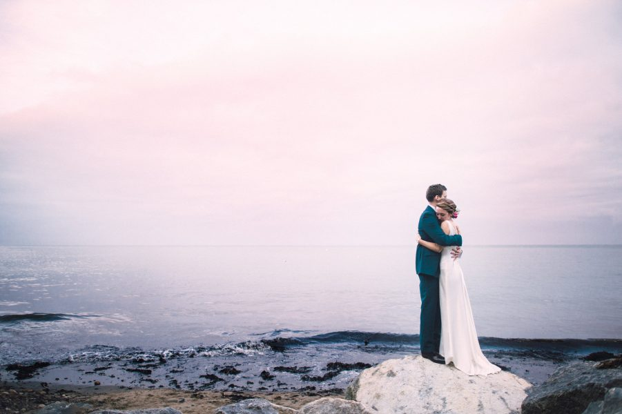 Fine Art portrait of Bride and Groom standing on a dramatic black rock hugging each other with the sea and pink clouds behind them at their relaxed creative cliff wedding Robins Hood Bay Yorkshire