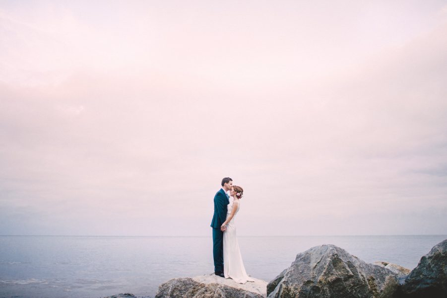 Fine Art portrait of Groom kissing Bride as they stand on a dramatic black rock hugging each other with the sea and pink clouds behind them at their relaxed creative cliff wedding Robins Hood Bay Yorkshire