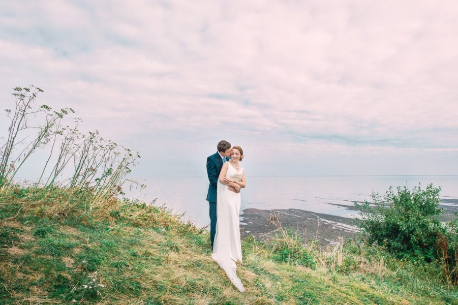 Fine Art portrait of Groom standing behind Bride wrapping his arms around hers as they stand on top of a dramatic cliff with the sea and pink clouds behind them at their relaxed creative cliff wedding Robins Hood Bay Yorkshire