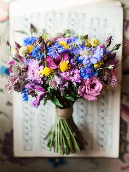Multicoloured blue pink and yellow bright wedding flowers bouquet styled on piano music sheet