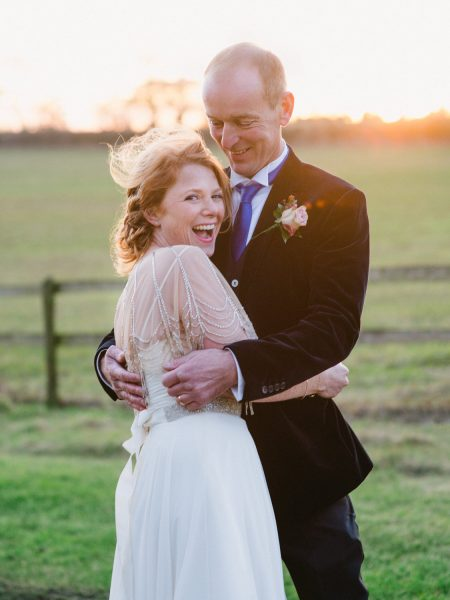 Fine art portrait of Bride in vintage tulle dress with scalloped beaded bolero snuggling a modern Groom in black velvet jacket laughing in front of a Winter sunset and fields at the Clocktower Winchester wedding