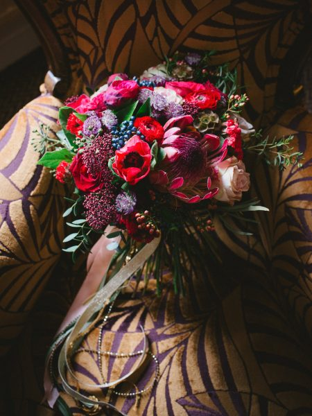 Fine art detail shot of Christmas wedding flowers bouquet by Catkin and Pussywillow featuring red bold dramatic florals at the Clocktower Winchester wedding