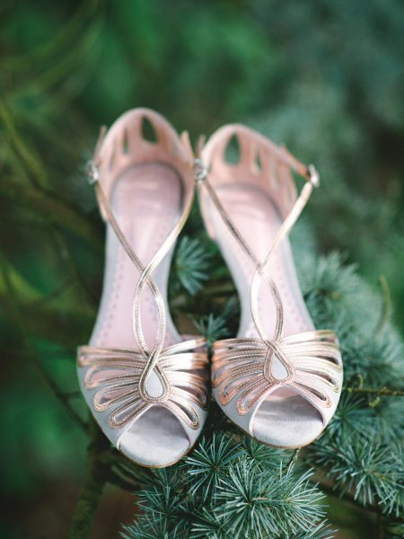 Fine art detail shot of metallic blush vintage wedding shoes styled in a pine tree Clocktower Winchester wedding