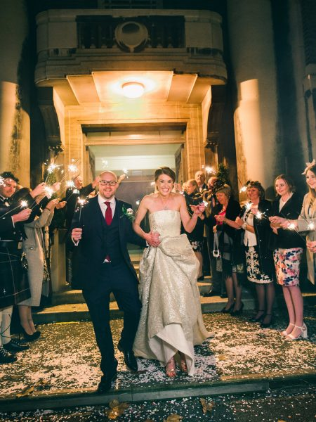 Sparkler shot of Bride in jesus Peiro dress and Groom exiting Art Deco East London registry office for their Winter wedding