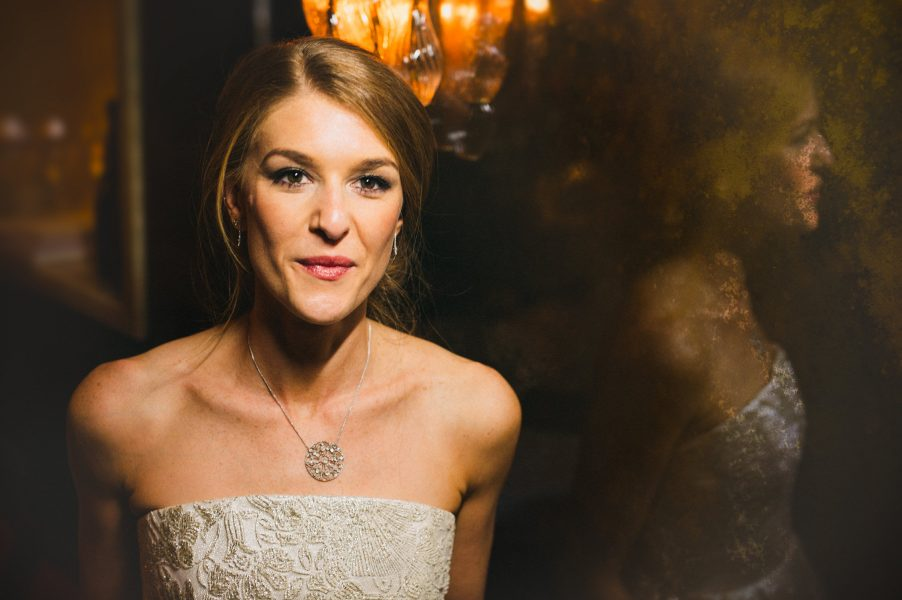 Fine Art portrait of Bride against a burnished texted rust vintage mirror and warm orange deco light for a Winter wedding at The Ivy London Covent Garden