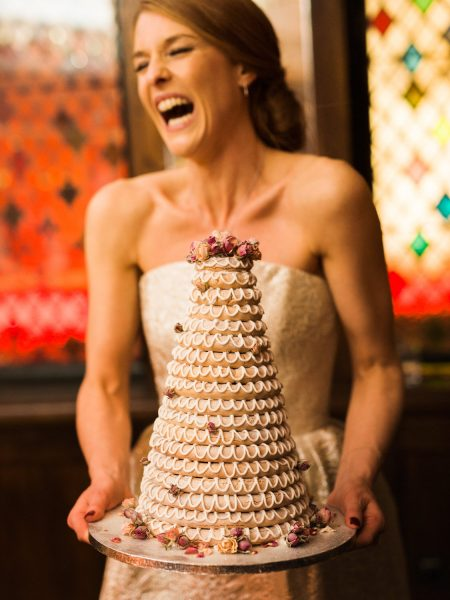Fine Art portrait of Bride holding Kransekake Scandinavian cake in front of stained glass windowing a warm orange deco light for a Winter wedding at The Ivy London Covent Garden