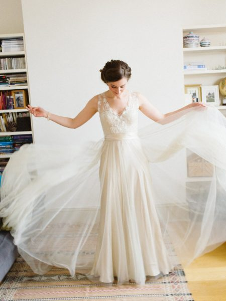 Fine Art Natural portrait of Bride looking down spreading wedding dress tulle layer in a dreamy way showing off it's soft sheer embellished champagne lace wedding details