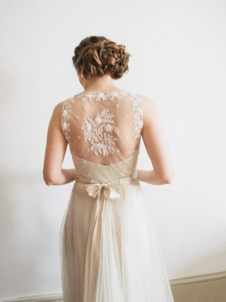 Fine Art Natural portrait of back of Bride looking down in a soft sheer with floral embroidery embellishment champagne coloured lace wedding dress