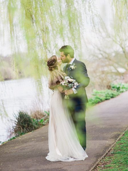Fine Art Natural portrait of Bride in champagne tulle dress and fur shrug kissing Groom in navy suit under dreamy weeping willow leaves on the back of the river thames near Mortlake Winter wedding