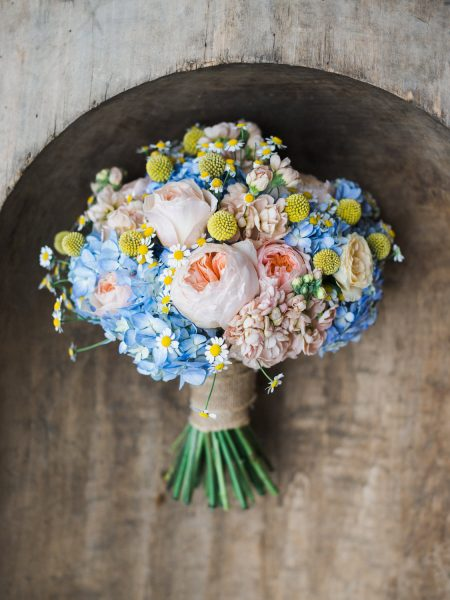 Bright and colourful happy blue yellow and peach floral wedding bouquet against rustic
