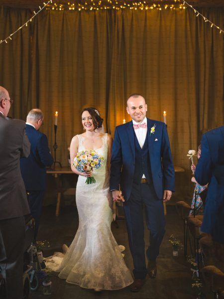 Joyful and happy Bride excite ceremony against fairy lights. Groom wears a navy suit and floral bow tie.