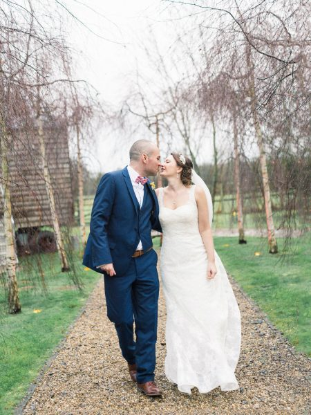 Fine art portrait of Bride and Groom walking towards camera with a lawn and silver birch trees behind them. Rainy Winter wedding