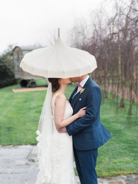 Fine art portrait of Bride and Groom kiss under Edwardian cram umbrella parasol with a lawn and trees behind them. Rainy Winter wedding