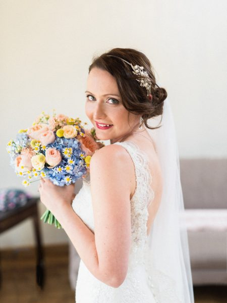 Fine Art Portrait of Bride smiling at camera with a bright and colourful happy blue yellow and peach floral wedding bouquet against rustic
