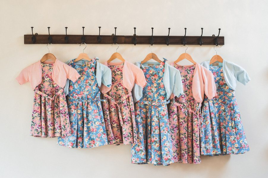 Bright and colourful happy bridesmaid flowergiel dresses hang in up. Pink and blue floral dresses hanging up on a rail during Bridal Preparations