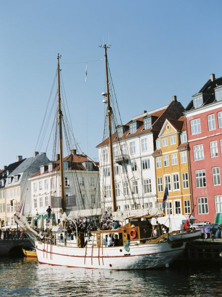Fine art Fuji 400s landscape of Nyhavn Copenhagen København Denmark featuring brightly coloured old buildings and old boats with large masts in sunshine