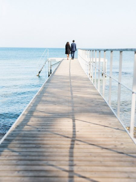 Engagement Couple at the end of a wooden walkway pier with sparking blue sea around them and the pier. Copenhagen København Skovshoved wedding