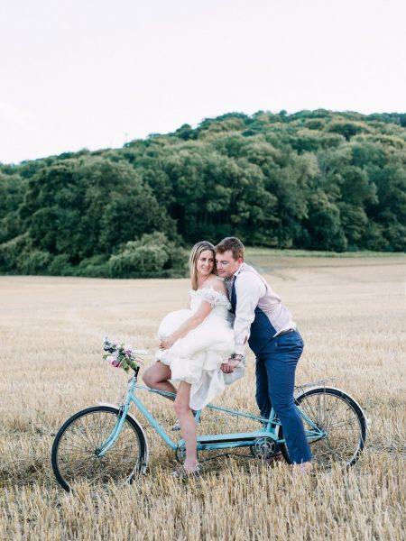 Fine Art portrait of a natural relaxed Bride in Ellie Sanderson dress and Groom on a blue tandem bike in a golden crop field West Sussex
