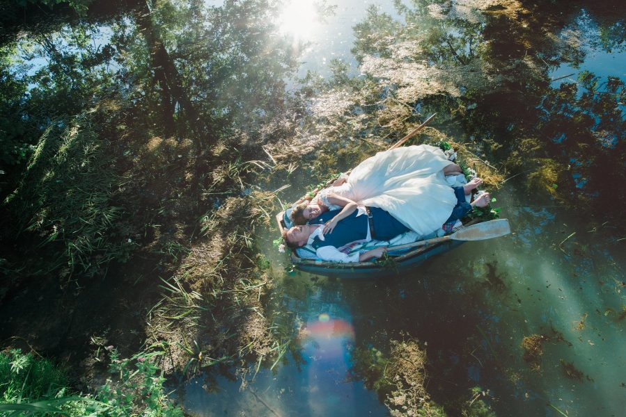 Fine Art portrait of a natural relaxed Bride in a Ellie Sanderson dress and Groom lying together on a rowing boat on dramatic lake covered in reflections West Sussex