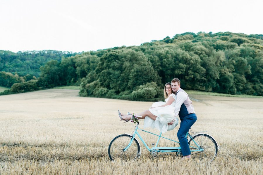 Fine Art portrait of a natural relaxed Bride sitting on the handlebars of a blue tandem bike in golden crop field featuring a Groom snuggled behind her sitting on bike seat West Sussex