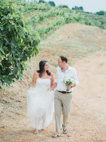 Fine Art Bride and Groom in flip flops and Summer suit walking towards camera with vineyard behind for a Destination wedding in a vineyard Algarve Portugal