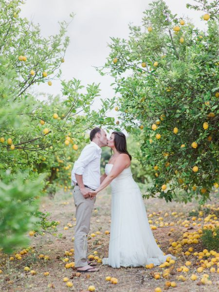 Fine Art Portrait of a couple kissing in a lemon grove Bride in tulle dress and Groom in flip flops and Summer suit from a Destination wedding in a vineyard Algarve Portugal
