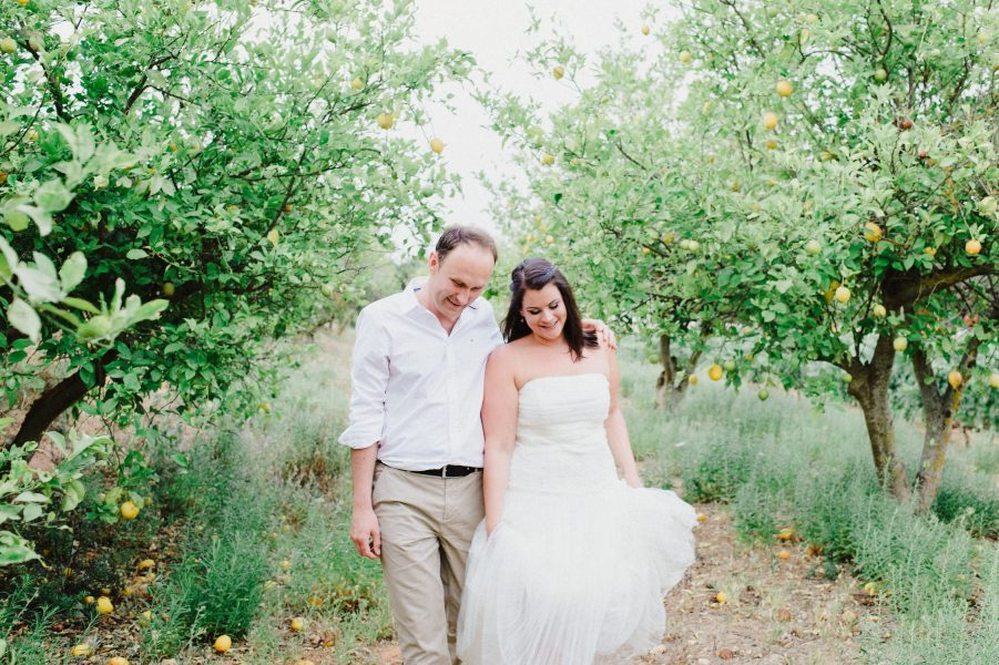 Natural Fine Art portrait of Bride and Groom walking through a lemon grove during a Destination wedding in a vineyard Algarve Portugal