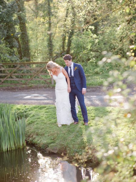 Fine art portrait of Bride and Groom naturally standing by the side of a lake as the sun sets Outwood Surrey