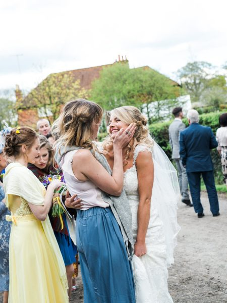 Guest congratulates Bride taking sweetly taking Bride's cheeks into her hands at wedding in Outwood Surrey