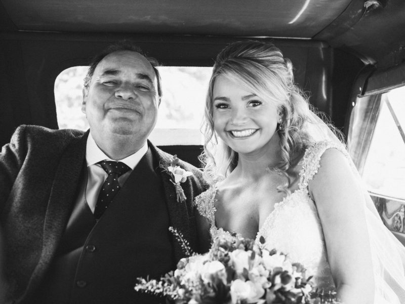 Black and white image of a Bride and father in vintage wedding car pre wedding ceremony