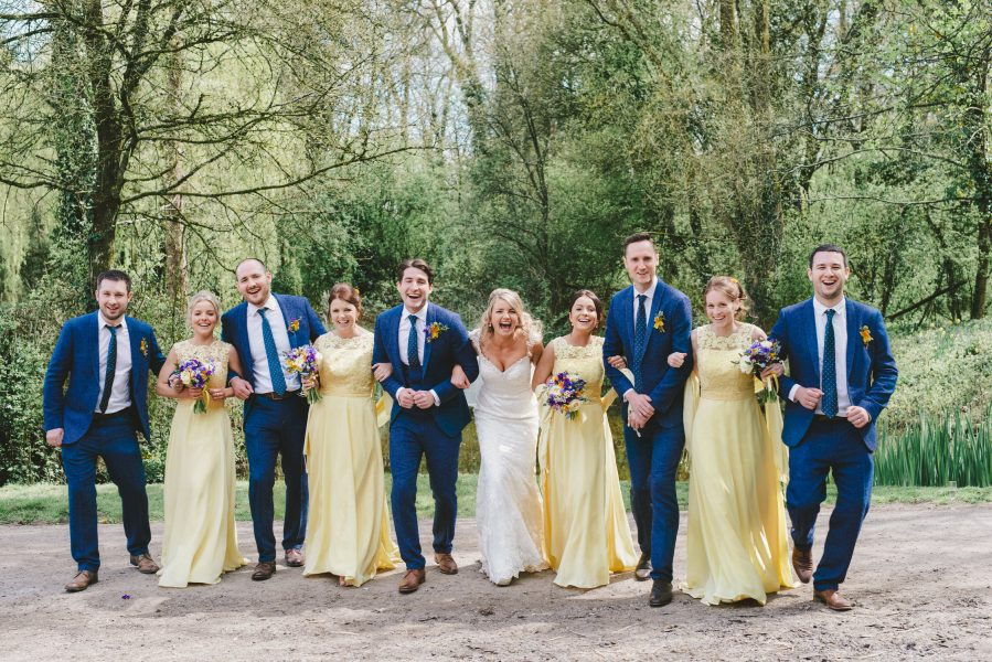 Bridal portrait of Bridesmaids in yellow dresses andu the Ushers and Best Man in blue tweed sits linking arms walking towards the camera at a wedding in Outwood Surrey