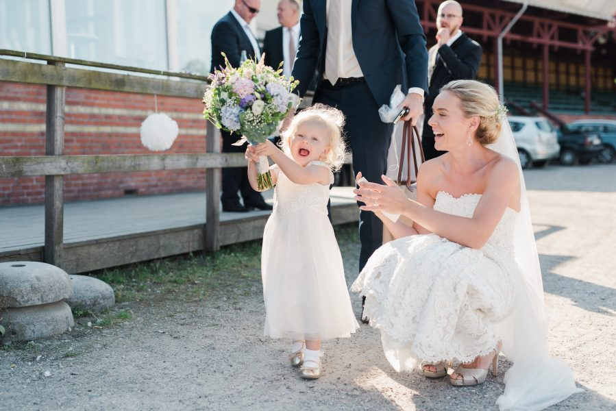 Fine art portrait of toddler flower girl running off with bridal bouquet while he Bride crouches next to her laughing Travbane Copenhagen