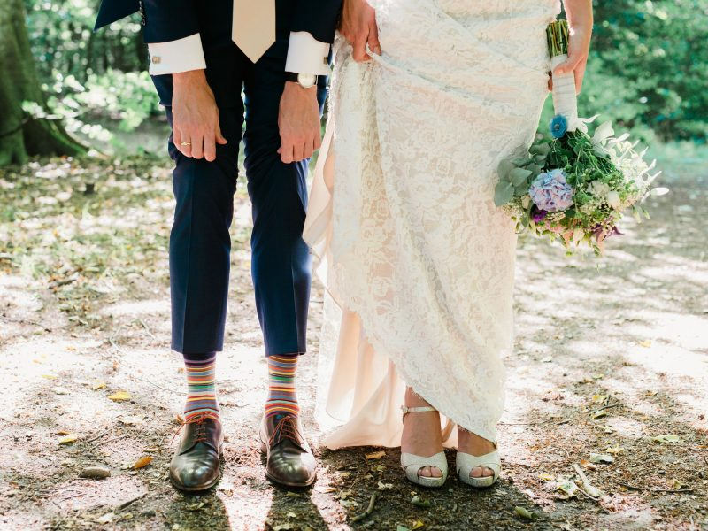 Fine art portrait of Bride's lace dress and shoes and the Groom's wedding shoes and stripy socks taken in a wood near Charlottenlund Travbane Copenhagen