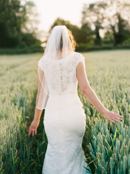 Close up of back of Bride as she walks walk from the camera through a tractor track in the corn for a country farm wedding