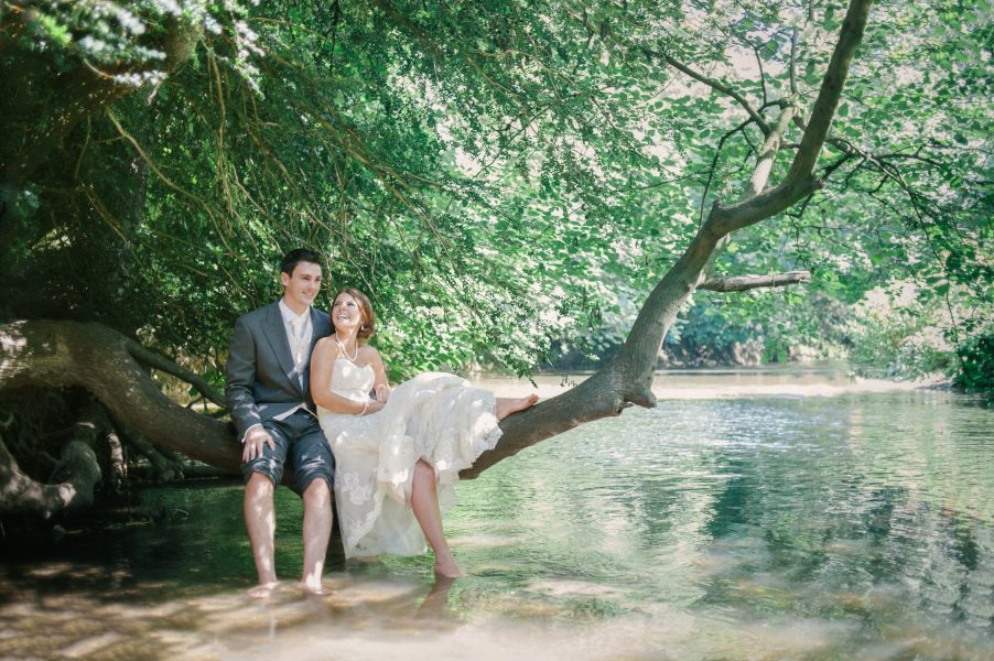 Bride lying against a Groom balanced on a tree growing over aqua water. Beautiful green summer leaves in wood in Surrey