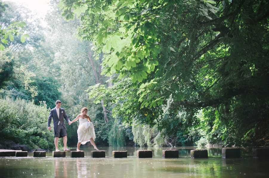 Bride leading Groom over a river via pretty stepping stones while the sun shines in a green wood in Surrey