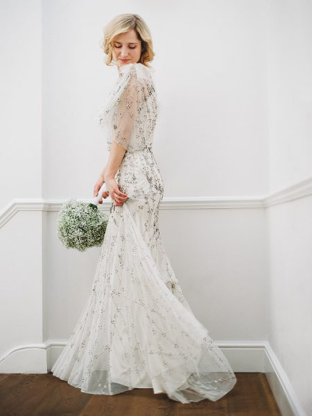 Fine Art bridal portrait of Bride twirling her dress looking down whilst holding her gypsophila bouquet wearing Jenny Packham crystal beaded one shouldered tulle dress for her London Gherkin wedding