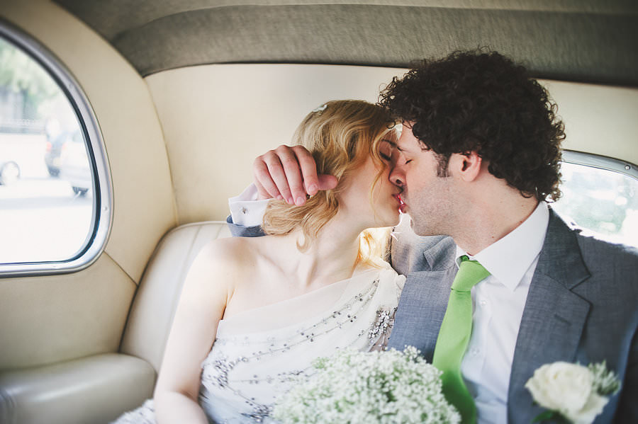 Bride in Jenny Packham beaded wedding dress tenderly kisses Groom as they make their way to the London Gherkin wedding