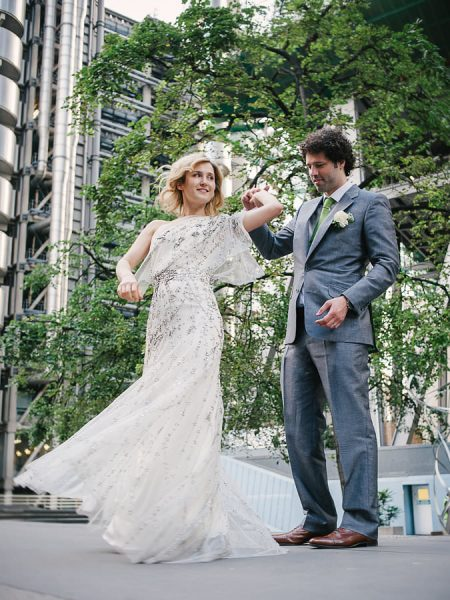 Close up of Groom twirling Bride in a Jenny Packham beaded dress under his arm outside the Gherkin for their london wedding