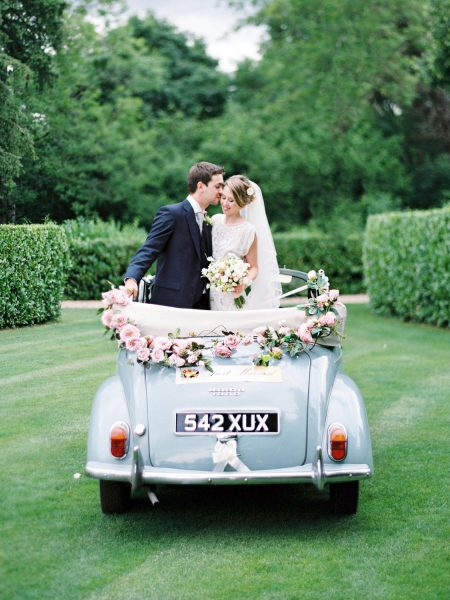 Fine Art Portrait of Bride and Groom standing in convertible powder blue Morris Minor with pink floral decoration on the lawn at Larmer Tree Gardens