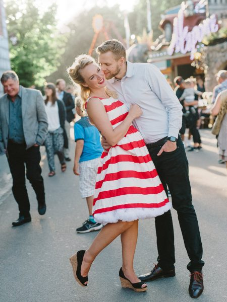 50s Retro Engagement Love Shoot of girl in red and white stripy dress being swept off her feet in a passionate kiss from her Fiancé with a crowded fairground scene with people walking in all directions Bakken Copenhagen Denmark
