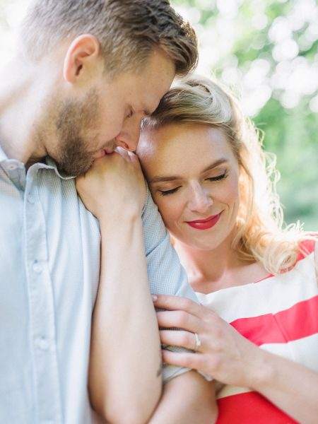 50s Retro Engagement Love Shoot of close up of a boy kissing the hand of his Fiancé while she holds his shoulder looking down