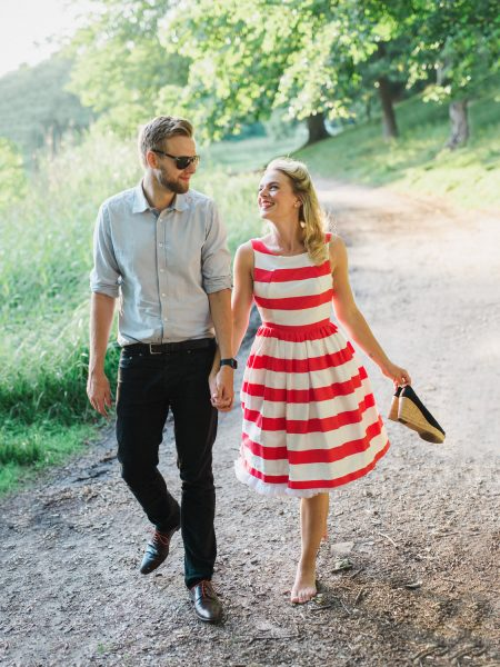 50s Retro Engagement Love Shoot of girl in red and white stripy dress walking with France in a woodland looking at each other Bakken Copenhagen Denmark